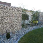 Gabionen Gartenmauer geschwungen mit Kies und grossen Steinen.