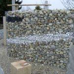 Gabionen Muster in Mauer mit Kies, grossen Steinen und Geröll.
