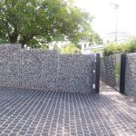 Schöne Gabionenmauer angrenzend zu bepflasterten Boden.