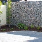 Gabionenmauer mit Pflanzenbewuchs.