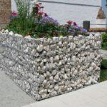 Kniehohe Gabionenmauer um Beet im Sommer.
